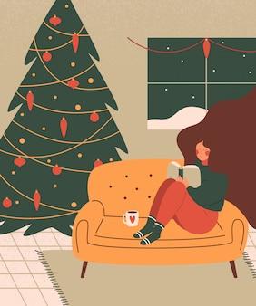 Una donna carina si rilassa con un libro in un accogliente salotto decorato per le vacanze di natale.