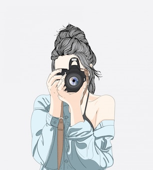 Una donna tiene una fotocamera elegante e indossa una giacca di jeans