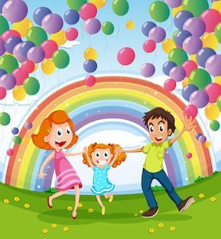 Una famiglia felice vicino all'arcobaleno e palloncini