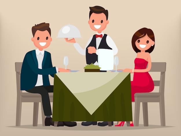 Una giovane coppia a cena in un ristorante. uomo e donna seduti a tavola, il cameriere ha portato un piatto.