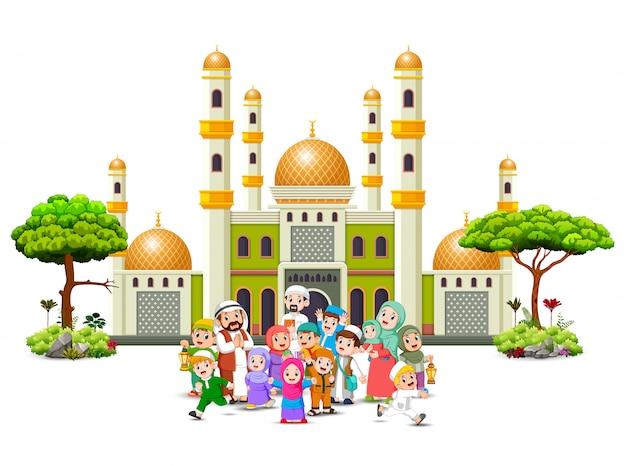 Una grande famiglia felice si sta radunando davanti alla verde moschea