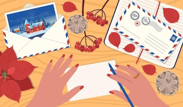 Una mano che firma una cartolina di natale. un concetto di spedizione di lettere, un biglietto di auguri per gli amici. un tavolo con busta postale con lettera, taccuino, viburno, coni, poinsettia.