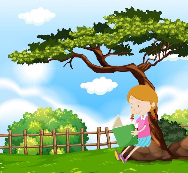 Una ragazza che legge un libro sotto l'albero