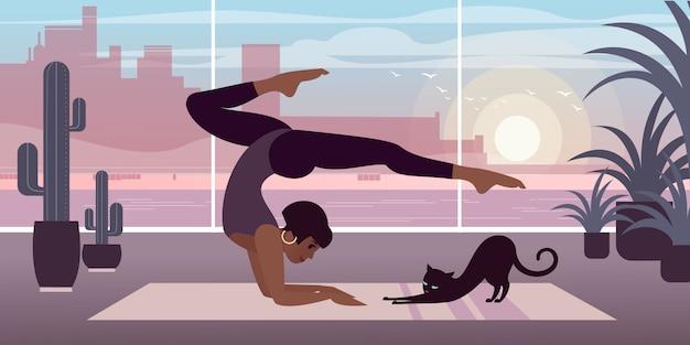 Una ragazza dalla pelle scura con gatto pratica yoga a casa.