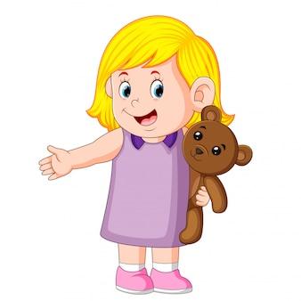 Una ragazza divertente che gioca con il tenero orsacchiotto marrone