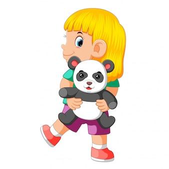 Una ragazza felice che gioca con la bambola del panda
