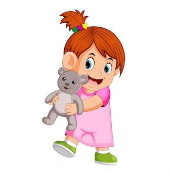 Una ragazza felice che gioca con un orsacchiotto grigio