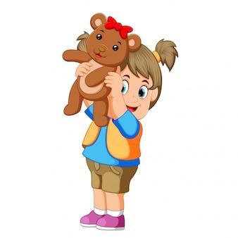 Una ragazza felice gioca con thw marrone orsacchiotto