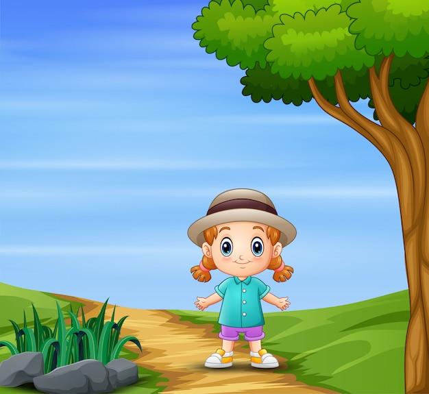 Una ragazza in cappello che cammina in natura