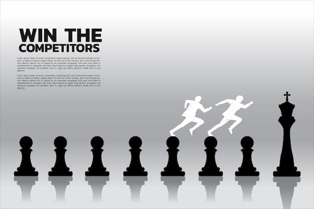 Una siluetta di un uomo d'affari due che corre sul pezzo degli scacchi