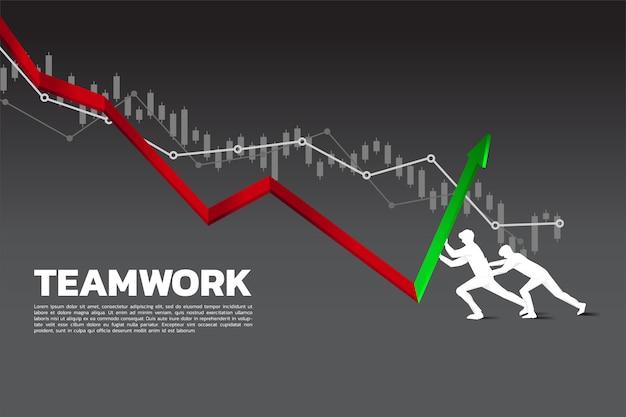 Una siluetta di un uomo d'affari due che spinge il grafico verso la direzione