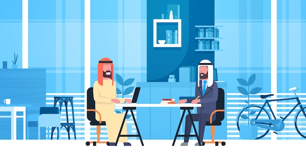 Uomini arabi di affari che si siedono alla scrivania nello spazio moderno di coworking che lavora insieme ai lavoratori musulmani nel centro dei colleghe