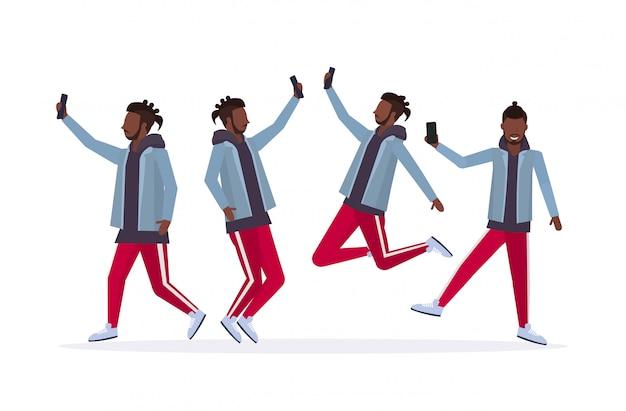 Uomini che prendono la foto del selfie sui personaggi dei cartoni animati maschii della macchina fotografica dello smartphone che fotografano in orizzontale bianco integrale del fondo bianco di pose differenti