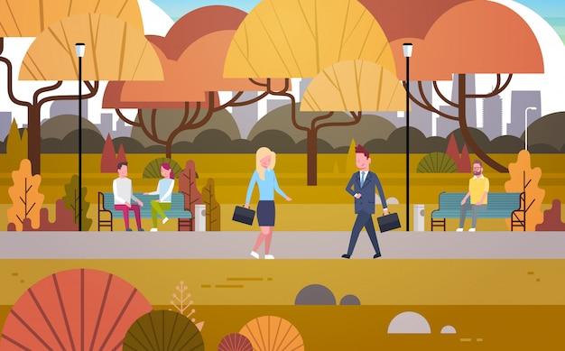 Uomini d'affari che camminano attraverso il parco di autunno sopra la gente che ha resto che si rilassa sedersi sulla panchina e comunicare all'aperto