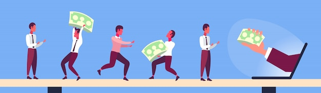Uomini d'affari che tengono le banconote del dollaro dal crowdfunding di reddito online dello schermo del monitor del computer portatile