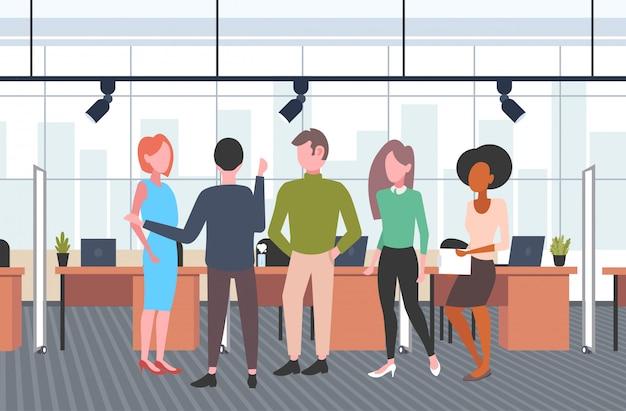 Uomini d'affari gruppo brainstorming mix gara uomini d'affari discutendo nuovo progetto durante la riunione colleghe casual in piedi insieme co-working spazio aperto interno orizzontale a figura intera