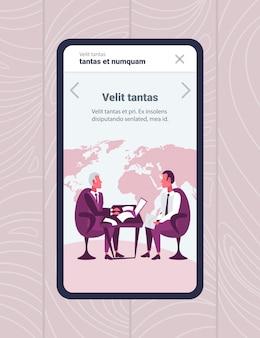 Uomini d'affari schermo mobile app seduti sul posto di lavoro online concetto di intervista di lavoro