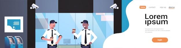 Uomini della guardia giurata che bevono caffè che lavora alla porta di entrata