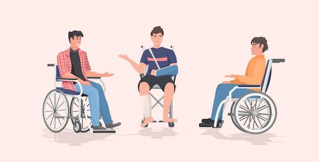 Uomini disabili seduti in sedia a rotelle