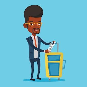 Uomo afroamericano di affari che mostra l'etichetta dei bagagli.