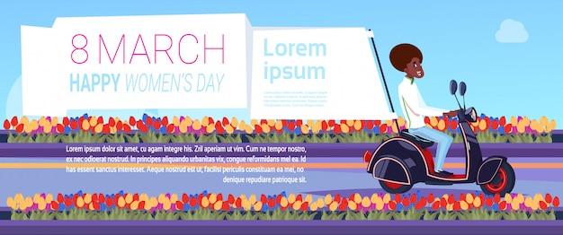 Uomo afroamericano sul motorino con il fondo internazionale felice creativo del modello di giorno delle donne dell'8 marzo dell'insegna