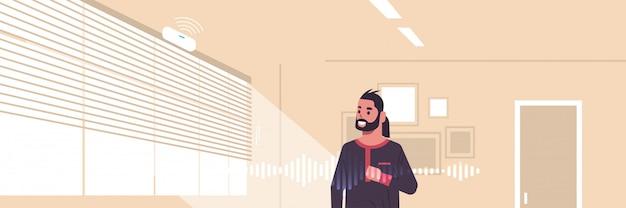 Uomo arabo che usando l'assistente digitale attivato riconoscimento vocale intelligente dell'altoparlante