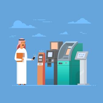 Uomo arabo che utilizza il pagamento mobile dello smart phone delle cellule di bancomat, uomo d'affari islam che indossa cl tradizionale