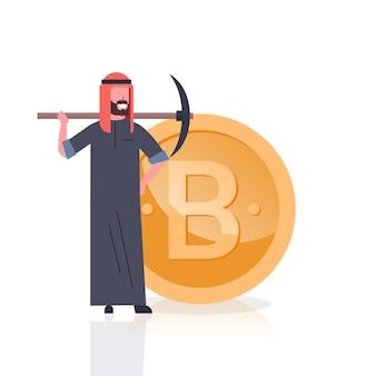 Uomo arabo di concetto di estrazione mineraria della criptovalvola con il piccone sopra la moneta dorata di bitcoin isolata
