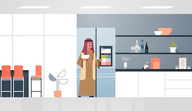 Uomo arabo toccando lo schermo del frigorifero con riconoscimento vocale dell'altoparlante intelligente