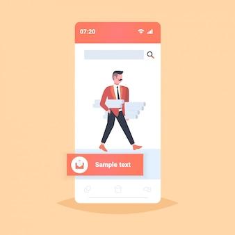 Uomo architetto holding arrotolato progetti ingegnere panning nuovo progetto architettura industria edile concetto appaltatore con progetti architettonici smartphone schermo mobile app integrale