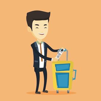 Uomo asiatico di affari che mostra l'etichetta dei bagagli.