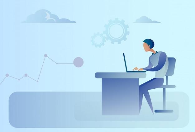 Uomo astratto di affari che si siede al computer portatile funzionante della scrivania
