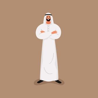 Uomo barbuto bello arabo in vestiti bianchi tradizionali in piedi con le braccia incrociate.