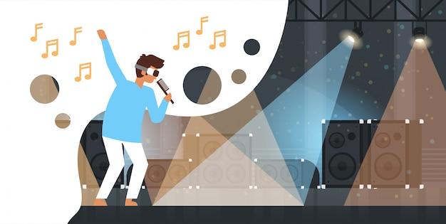 Uomo cantante indossare occhiali per realtà virtuale tenere il microfono sul palco con effetti di luce discoteca studio attrezzatura musicale vr vision headset headset