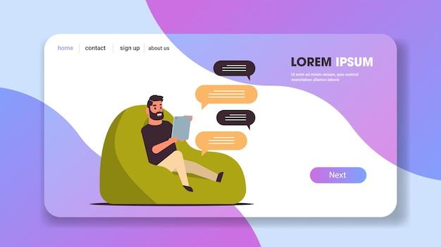 Uomo casual in chat messaggistica con ragazzo tablet seduto al sacchetto di fagioli utilizzando la comunicazione bolla di chat di rete sociale app mobile