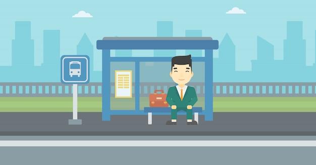 Uomo che aspetta autobus alla fermata dell'autobus.