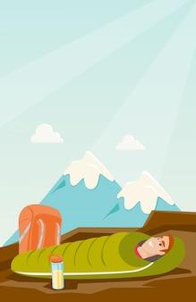 Uomo che dorme in un sacco a pelo in montagna.