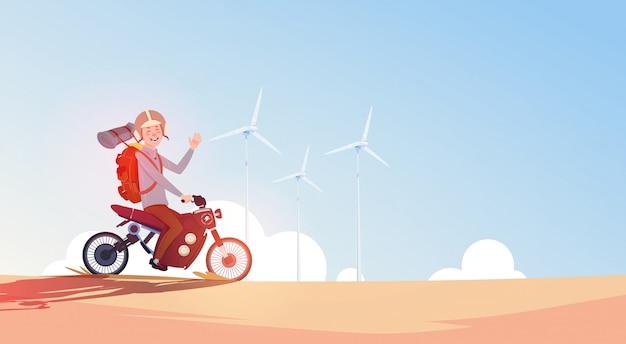 Uomo che guida fuori dalla bici della strada nel viaggio del ragazzo del casco sul motociclo sopra cielo blu con le turbine eoliche
