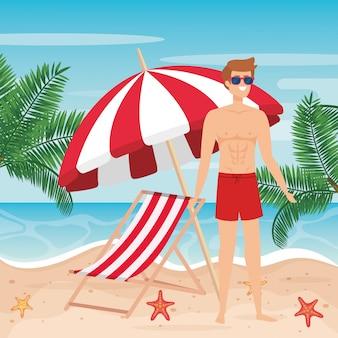 Uomo che indossa pantaloncini da bagno con occhiali da sole e sedia abbronzante con ombrello