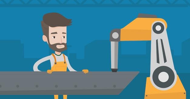 Uomo che lavora al braccio robotico di saldatura industriale.