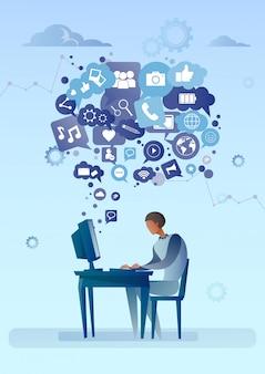 Uomo che per mezzo del computer con la bolla di chiacchierata del concetto sociale di comunicazione della rete delle icone di media