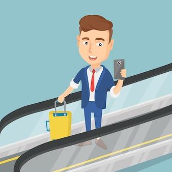 Uomo che per mezzo dello smartphone sulla scala mobile all'aeroporto.