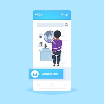 Uomo che rade la sua faccia ragazzo afroamericano guardando specchio moderno bagno di casa interni smartphone schermo mobile app vista posteriore integrale