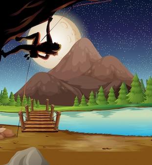 Uomo che si arrampica sulla roccia durante la notte di luna piena