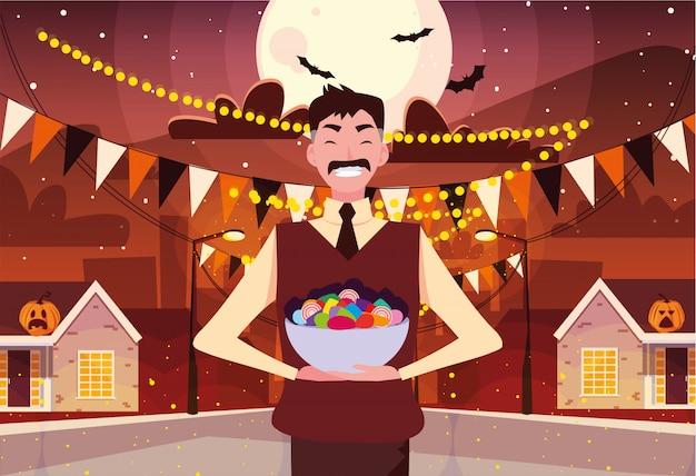 Uomo con caramelle nella notte di halloween