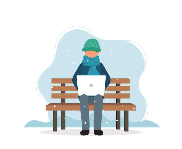 Uomo con il computer portatile che si siede sul banco in inverno.