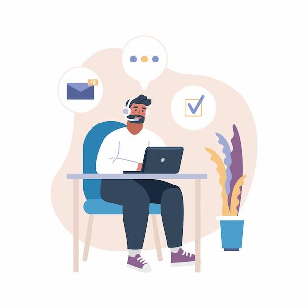Uomo con l'auricolare che lavora con il computer portatile