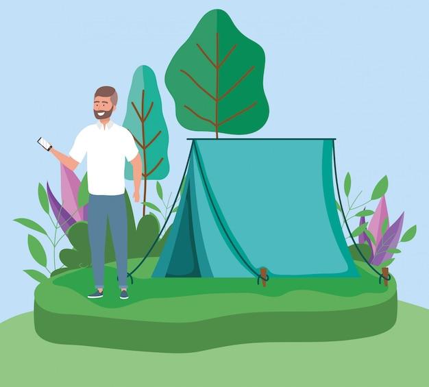 Uomo con la foresta di picnic di campeggio della tenda dello smartphone