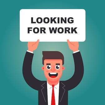 Uomo con un cartello in mano in cerca di lavoro