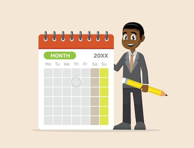 Uomo d'affari africano che progetta sul calendario con la matita.